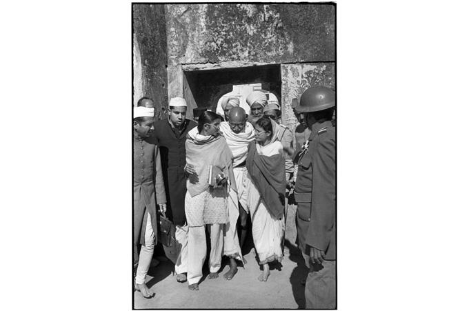 """Gandhi på vei ut fra en muslimsk helligdom i Mehrauli, hjulpet av """"stokkene"""" sine Manu Gandhi (t.v.) og Abha Gandhi (t.h.). Det var en av de siste gangene han viste seg offentlig, fra fasten var over til han døde. Delhi, India. 27. januar 1948. Foto: Henri Cartier-Bresson / Magnum Photos/All Over Press"""
