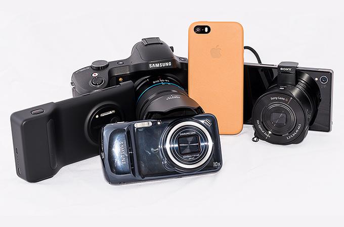 Hva velger du? Et kamera eller mobilen? Eller begge deler på en gang? Fotografi er i gang med en stor test av kombinerte kameraer og mobilenheter. Bak fra v. Nokia Lumia 1020, Samsung Galaxy NX, Apple iPhone 5S og Sony Xperia Z1. Foran Samsung Galaxy S4 Zoom.