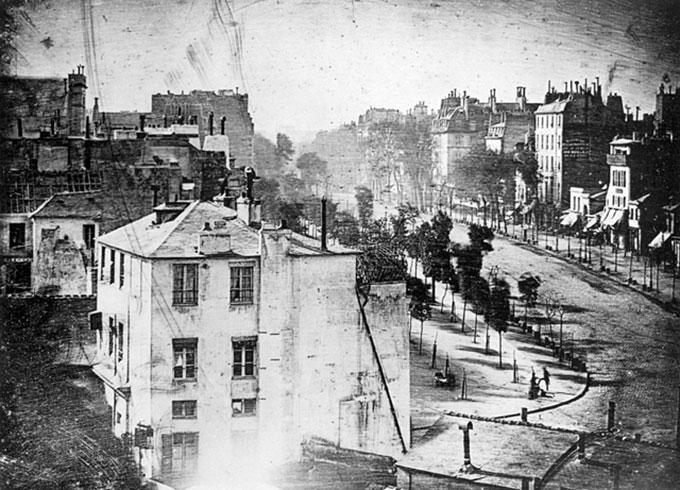 Daguerres fotografi fra 1838, tatt fra taket av bygningen hvor laboratoriet hans lå og som siden er revet og erstattet av mer moderne bygg, er her speilvendt for å samsvare med virkeligheten (daguerreotypiene var speilvendte). Mannen som ble det første menneske i et fotografi står nede til høyre.