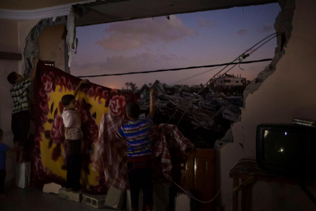 Bildetekst: Barna i Haraara-familien i Gaza henger opp tepper for å skjule ruinene utenfor soverommet dems. Familien har flyttet tilbake i leiligheten siden de ikke har noe annet sted å bo. Nabolaget deres ble svært ødelagt av krigen i sommeren 2014. Totalt ble over 100.000 hjem ødelagt eller skadet.