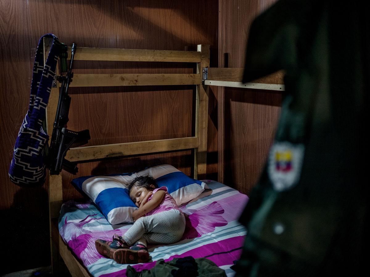 Gerilja-leiren El Diamante, Caquetá- provinsen: Sara Manuela (2) sover omgitt av en FARC-uniform og et gevær. Gerilja- soldater har egentlig ikke lov til å ha barn, men foreldrene hennes tror på en fredsavtale og har tatt sjansen. Hvis fredsprosessen mislykkes må de overlate henne til bestemoren, sider de. © Mads Nissen / Politiken for Nobels Fredssenter