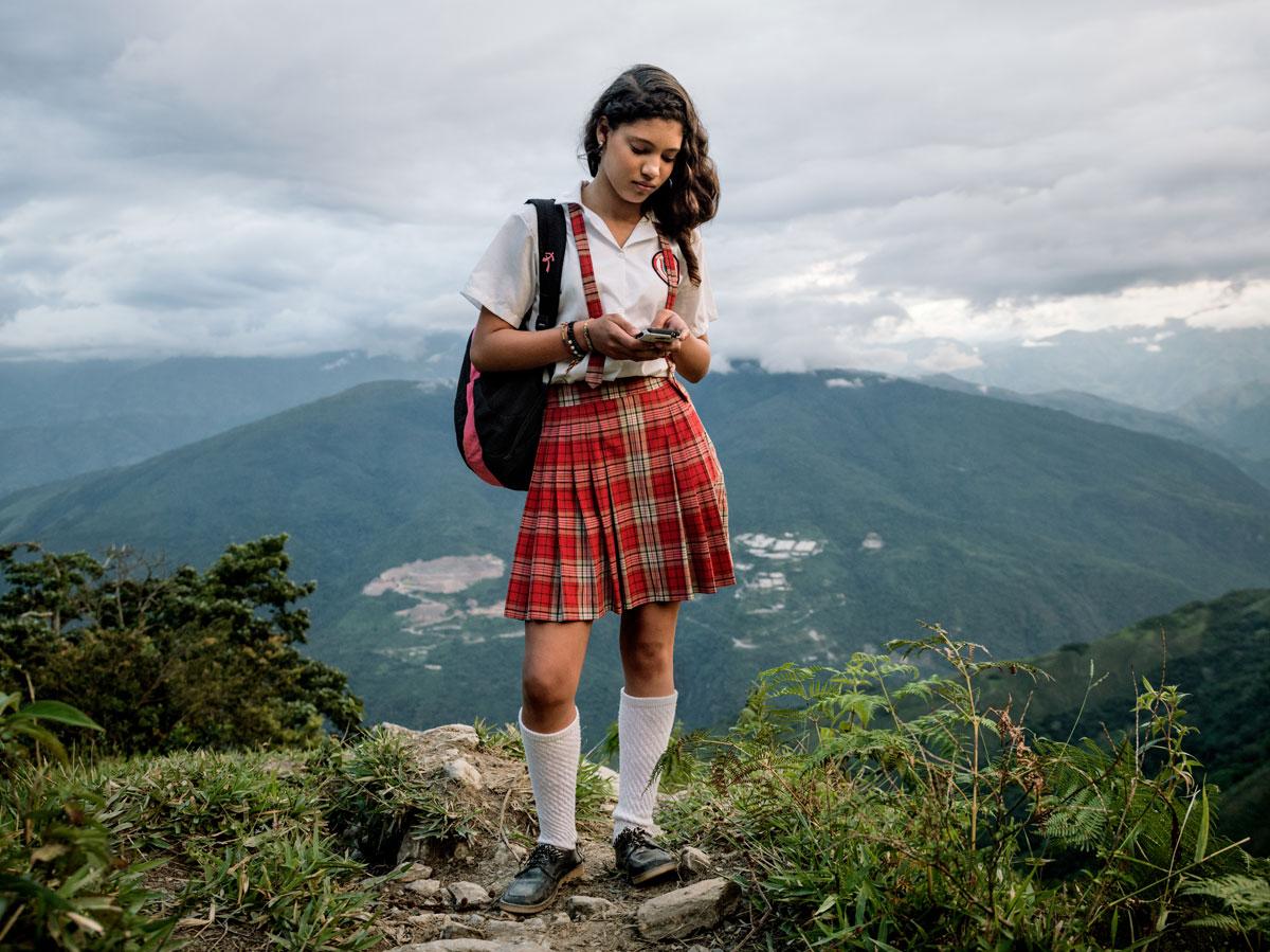 El Orejon, Antioqui-provinsen: Alexandra Mazo (12) med mobiltelefonen sin på vei nedover fjellet etter skolen.Området hun bor i er sterkt berørt av konflikten. Væpnede grupper så vel som narkotikaprodusenter opererer åpenlyst her. © Mads Nissen / Politiken for Nobels Fredssenter